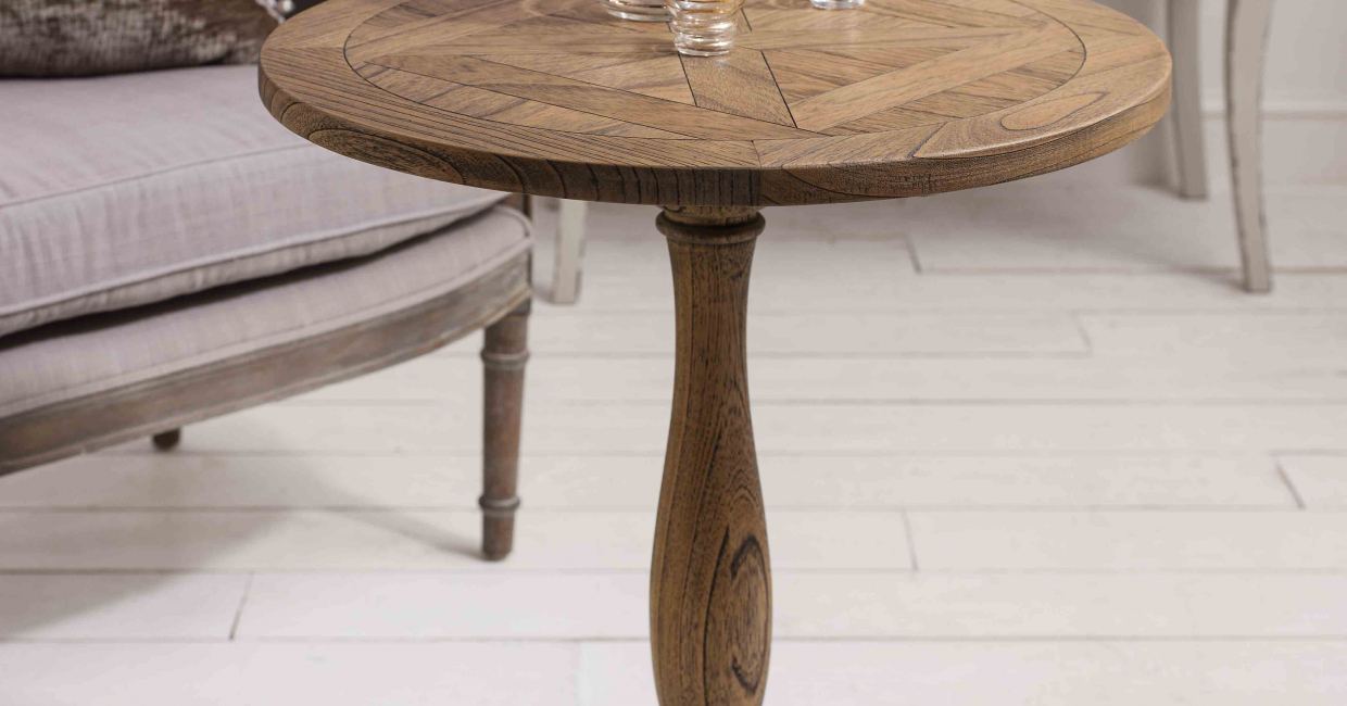 The Dexter parquet side table boasts a dry, weathered finish and inlaid parquet top